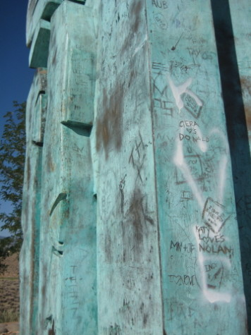Graffiti is scratched in and spraypainted on the statue.